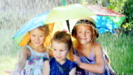 three sisters are hiding under the umbrella of color. There is a warm summer rain, the children are happy video