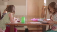 Three sisters coloring at a kitchen table video