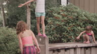 Three sisters play on a short wall in a park video