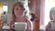 Three sisters sitting at a kitchen counter with large mugs and waiting for breakfast video