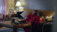 Three sisters sitting on a couch sharing a blanket and watching TV video