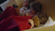 Three sisters sitting on a couch sharing a blanket choosing what to watch on TV video