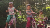 Three sisters sitting on their bikes and smiling video