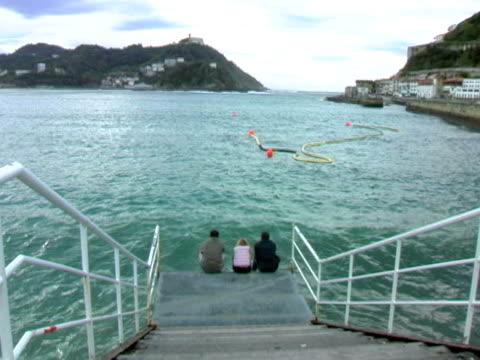 Three sitting on dock of San Sebastian Spain video
