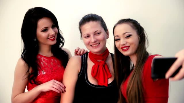 Three smiling cheerful girls making selfie video
