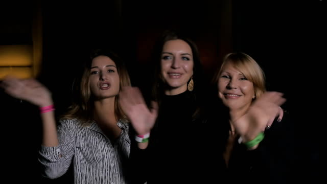 Three smiling women waving hands and send a kiss into the camera video