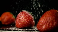 Three strawberries in a row on a black table. Slow mo video
