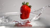 Three strawberries plung into water video
