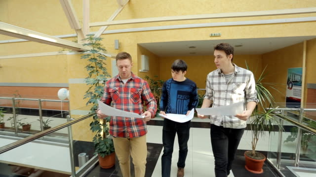 Three student walk with blueprint inside university of art video