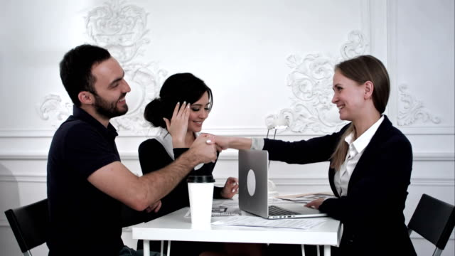Three successful business partners shaking hands and smile in the office video