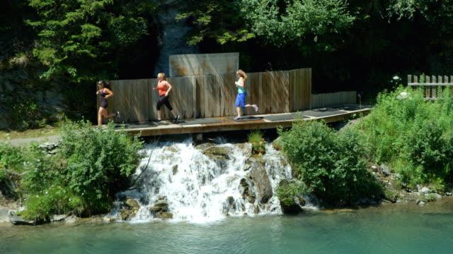 Three very diverse adult women running across a bridge over a waterfall. video