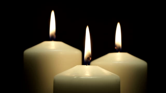 Three white candles burning in the dark video