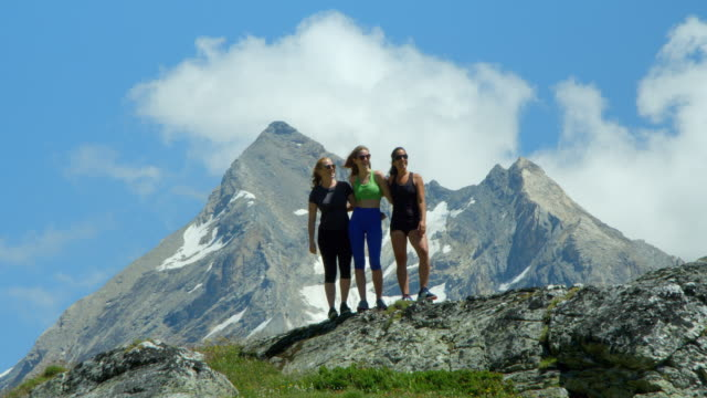 Three women celebrate an adventure in the mountains. video