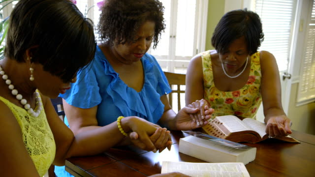 three women hold hands in prayer video