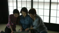 Three women looking at a digital tablet video