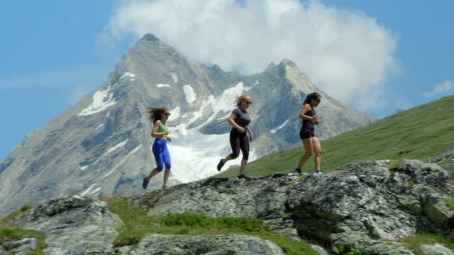 Three women run across a snow capped mountain range. video