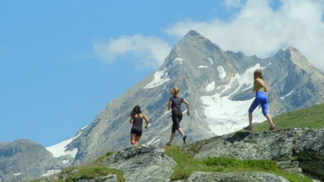 Three women run up a high altitude mountain range. video
