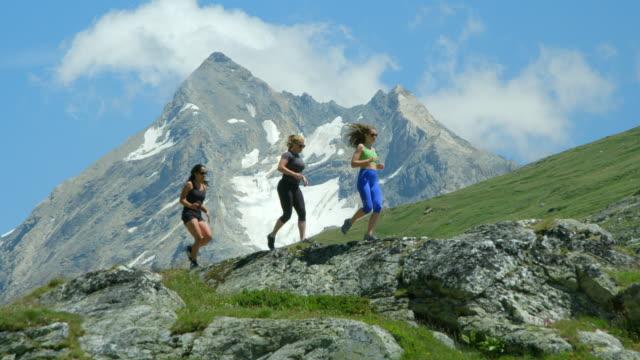 Three women running across a mountain range. video