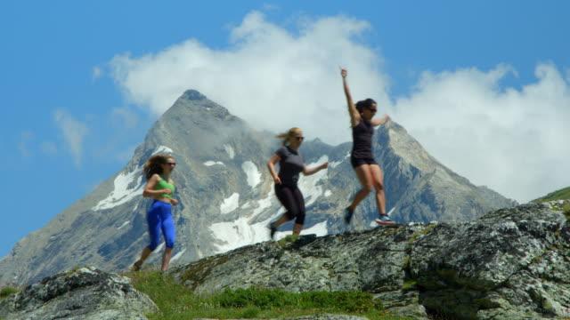 Three women running through mountains celebrate their success. video