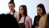 Three women stands in art studio and listen to information video