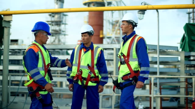 Three workers in production plant as team discussing, industrial scene in background video