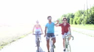 Three young adults having fun cycling and taking selfies video