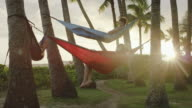 Three young adults relaxing in hammocks among palm trees video