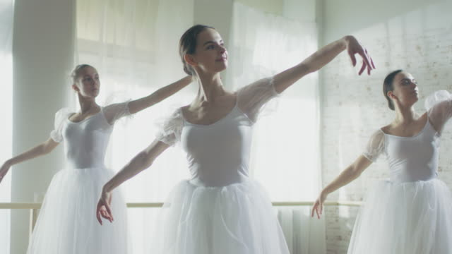 Three Young and Gorgeous Ballerinas Synchronously Dancing. They Wear White Tutu Dresses. Shot on a Sunny Morning in a Bright and Spacious Studio. In Slow Motion. video