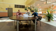 Three young architects sit at round wooden table and look at graphic video