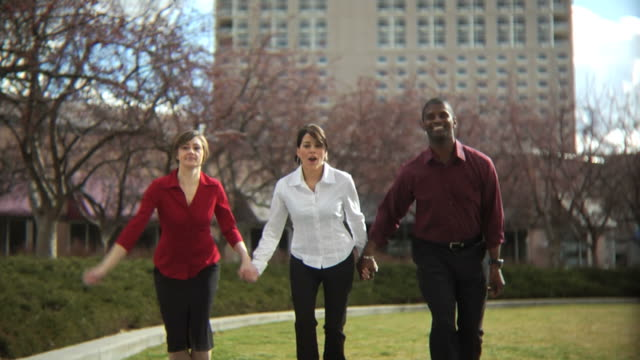 Three young business people jumping video