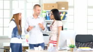 Three young coworkers standing and talking at workplace video
