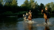 SLOW MOTION: Three young girls riding horses against stream of water video