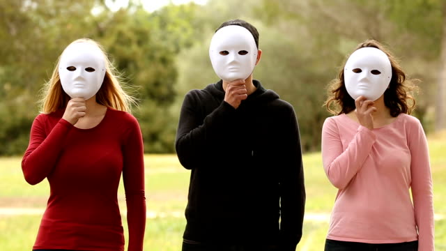 three young people with mask looking each other video