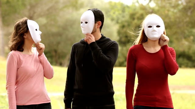 three young people with mask looking video