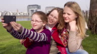 Three Young Teenage Girls, sisters, taking selfies outdoors, near river video