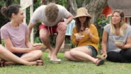 Three young woman and a young man sitting in the grass eating fruit dishes video