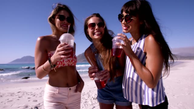 Three young women friends having drinks at the beach video