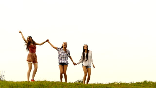 Three young women holding hands and having fun,slow motion video