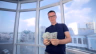Throwing money in to air. Businessman counting us dollars, throwing it in the air video