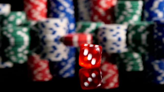 Throwing red dice on the background of poker chips. Slow video