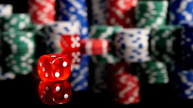 Throwing red dice on the background of poker chips. Three video