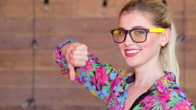 Thumbs down by attractive young women in glasses video
