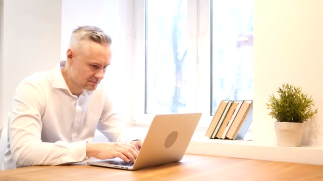 Thumbs Down by Middle Age Man while Working on Laptop video