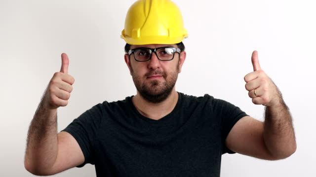 Thumbs-up portrait of construction worker on white background video
