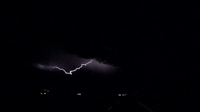 SLOW MOTION: Thunderstorm lightning bolt striking over traffic road video