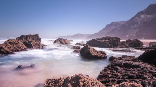 Tide sea blue water on rocky shore. Sea breeze above waves splash video