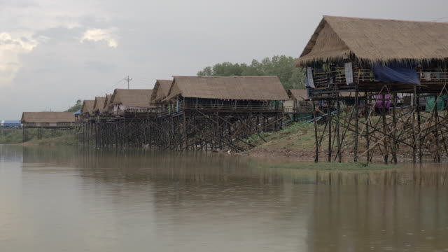 Tidy row of waterfront stilt-houses with rain falling over lake video