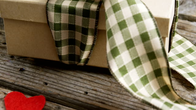 Tied gift box and happy fathers day card on wooden plank video