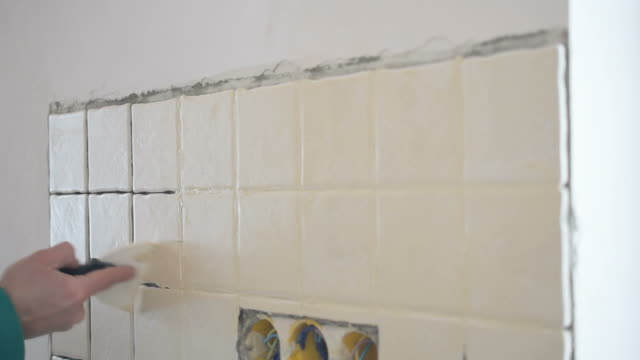 Tile worker filling crevices between tiles with grout video