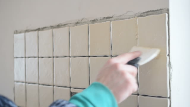 Tile worker filling gaps between tiles with grout video